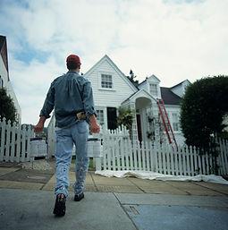 carpenter walking up to house