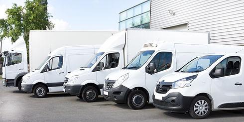 Several cars vans trucks parked in parking lot for rent or delivery.jpg