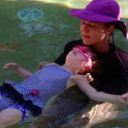 young child learning to float on back with private swim instructor