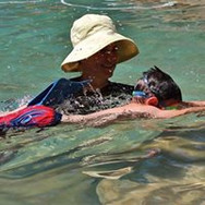 young boy learning to swim with an instructor
