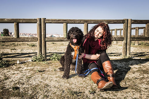 Doctor Loulittle sitting in a park with her black Spanish Water Dog Cailín ¦ English & Spanish dog training in Madrid and online