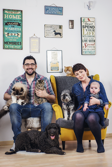 A family of a man, a woman and a baby sit with their three cats and two dogs ¦ English & Spanish dog training in Madrid and online
