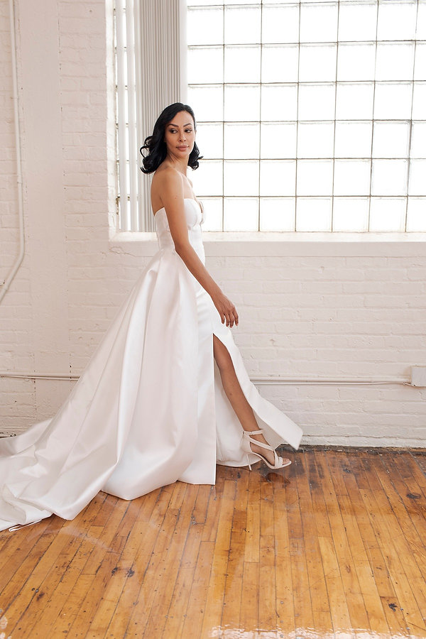A stunning, sleeveless Mikado bridal gown with center leg slit and sweetheart neckline on model strutting walking at photoshoot.