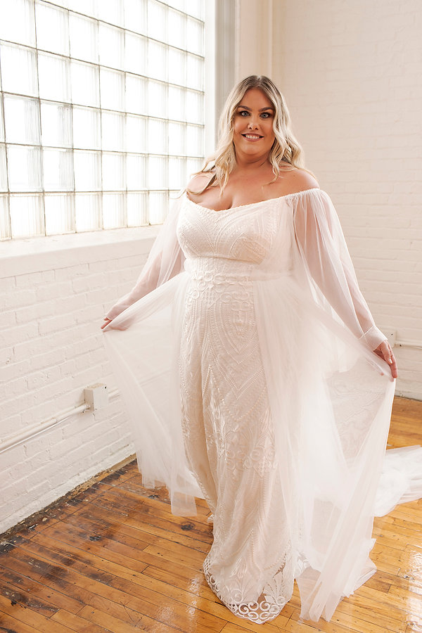 Curvy model wheres boho long sleeve etheral lace embroidered wedding gown. off the shoulder wedding dress with long train.