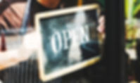 Man putting on shop open sign.jpg