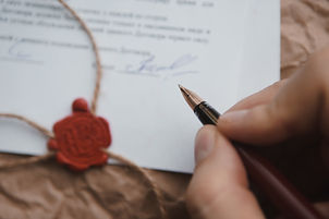 Close up of hand signing a Last Will and