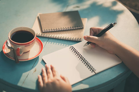 Woman right hand writing journal on smal