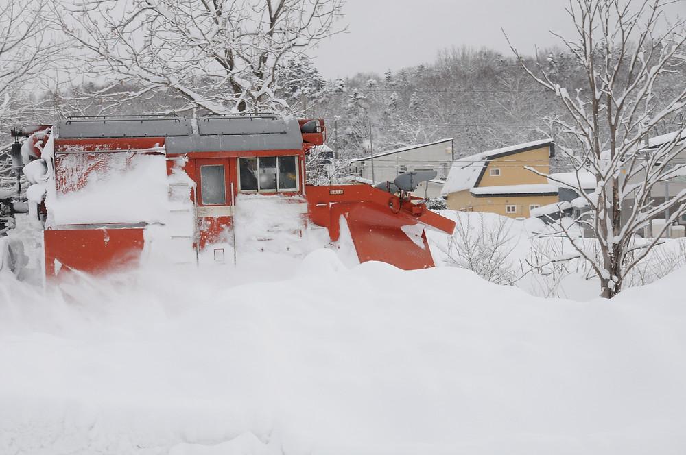 我が家の庭の雪山からウィングを広げたラッセル車を撮影