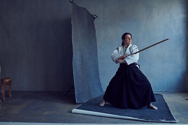 Foto docent Esther in hakama met boken (houten zwaard) voor grijze achtergrond. Foto uit KEK mama