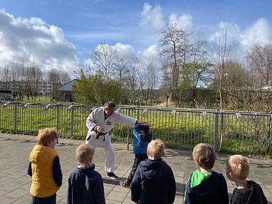 Meester Sam doet een oefening om te blokken voor op een kind, terwijl de andere kinderen toekijken