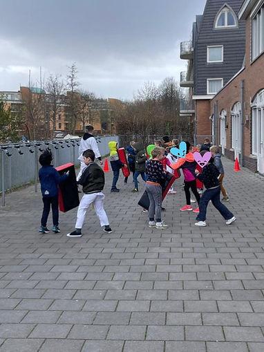 Kinderen oefenen stoot- en traptechnieken op schopkussens tijdens de les