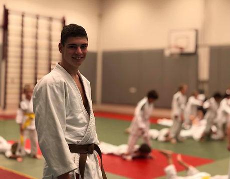 Docent Alessi met op de achtergrond een groepsles jujutsu voor kinderen tijdens de warming-up