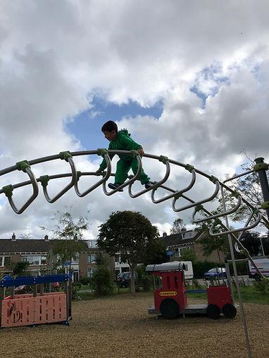 Kind op hoog klimrek vertoont coole kunsten