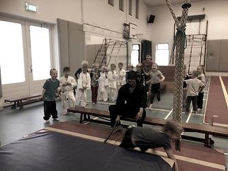 Meester Sam als ninja met een blinddoek en zwaard terwijl de kinderen langs hem sluipen