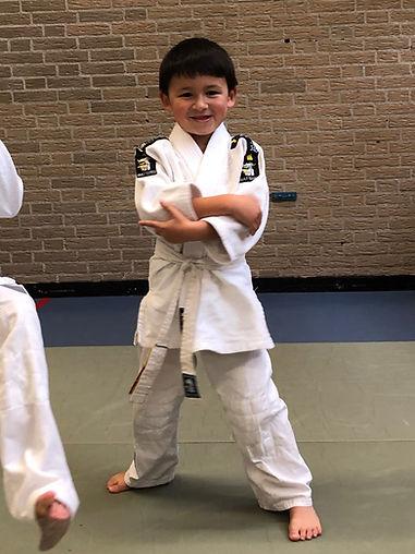 Zelfverzekerd kind in judopak met zijn armen over elkaar