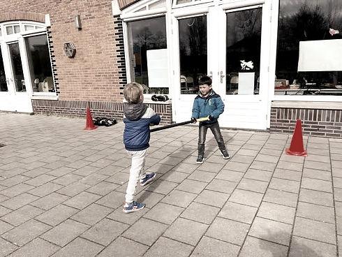 Twee kinderen houden een gevecht met oefenzwaarden (zachte stokken)