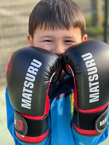 Blij en zelfverzekerd kind met bokshandschoenen bij zijn wangen waar hij net overheen kijkt