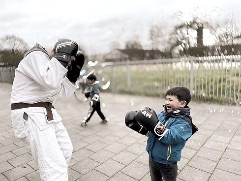 Blij kind met bokshandschoenen mag een oefening doen met meester Alessi