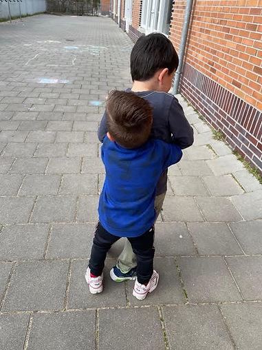 Staand stoeien - een kind houdt de ander van achter vast, de ander probeert te ontsnappen