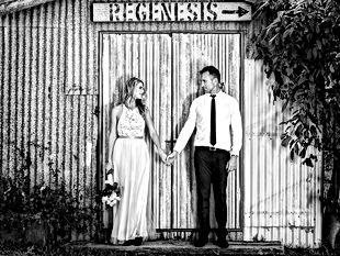 Brde and groom stading at rutic barn door