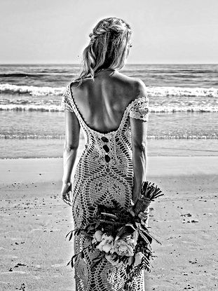 Bohemian bride walking barefoot on the sand