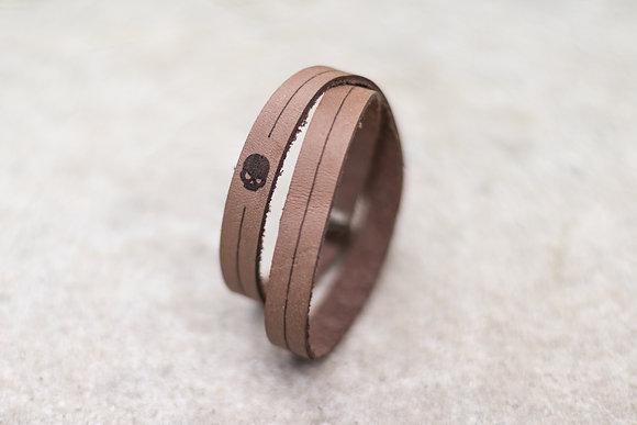 Bracelet en cuir double tour sur fond béton motif tête de mort