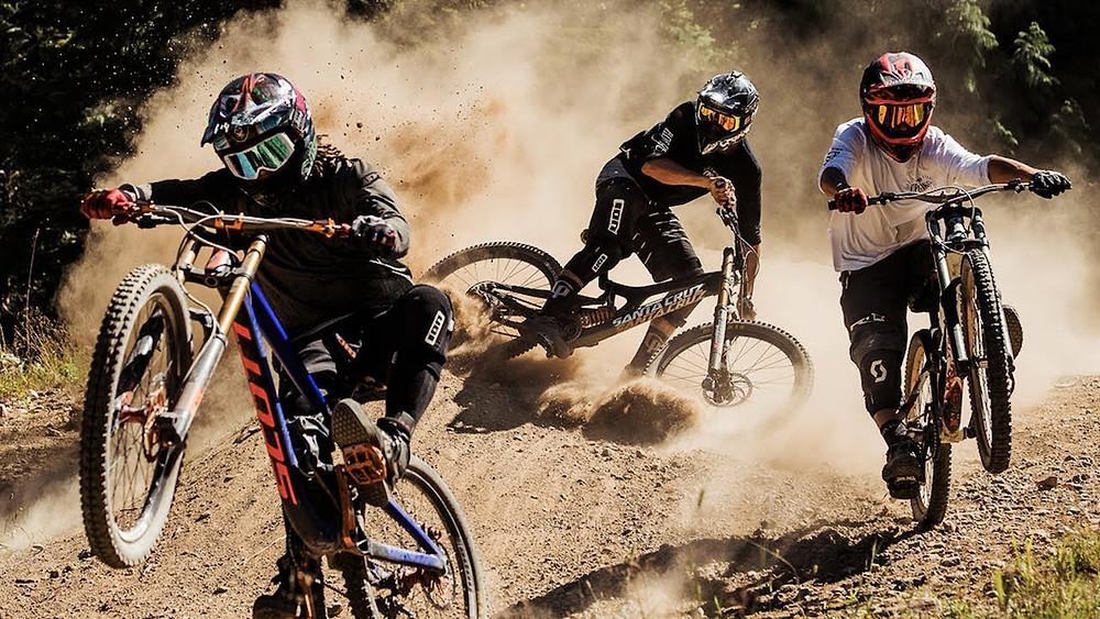 Three men freeride down loose hill