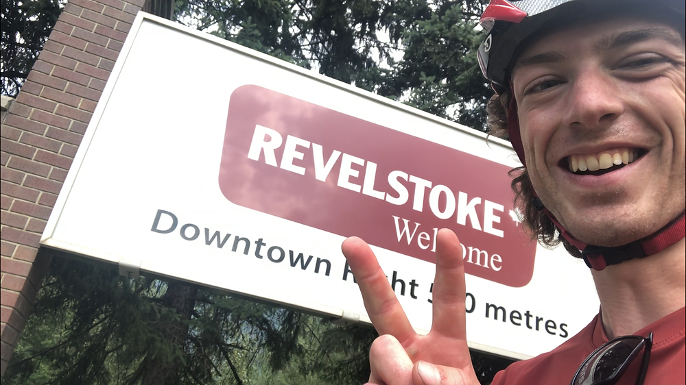 Evan Mant in front of the Welcome sign in Revelstoke BC during his Biking trip across Canada