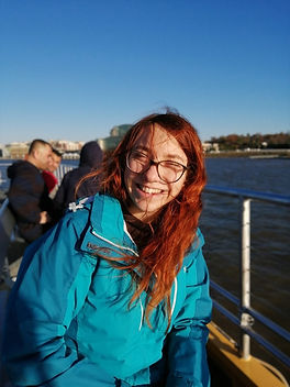 Woman with long red hair and glasses standing on a boat