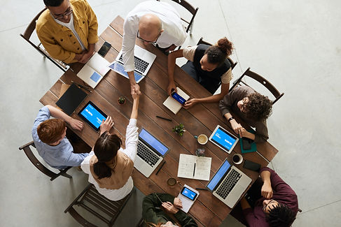 Top down view of business professionals meeting with laptops at a wood table