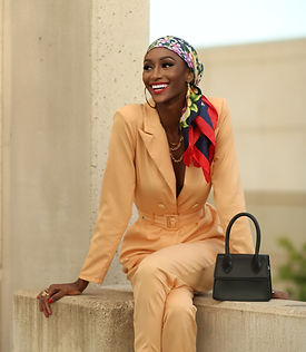 Cole Woods smiling, sitting on a concrete ledge wearing a yellow jumpsuit and multicolor head scarf