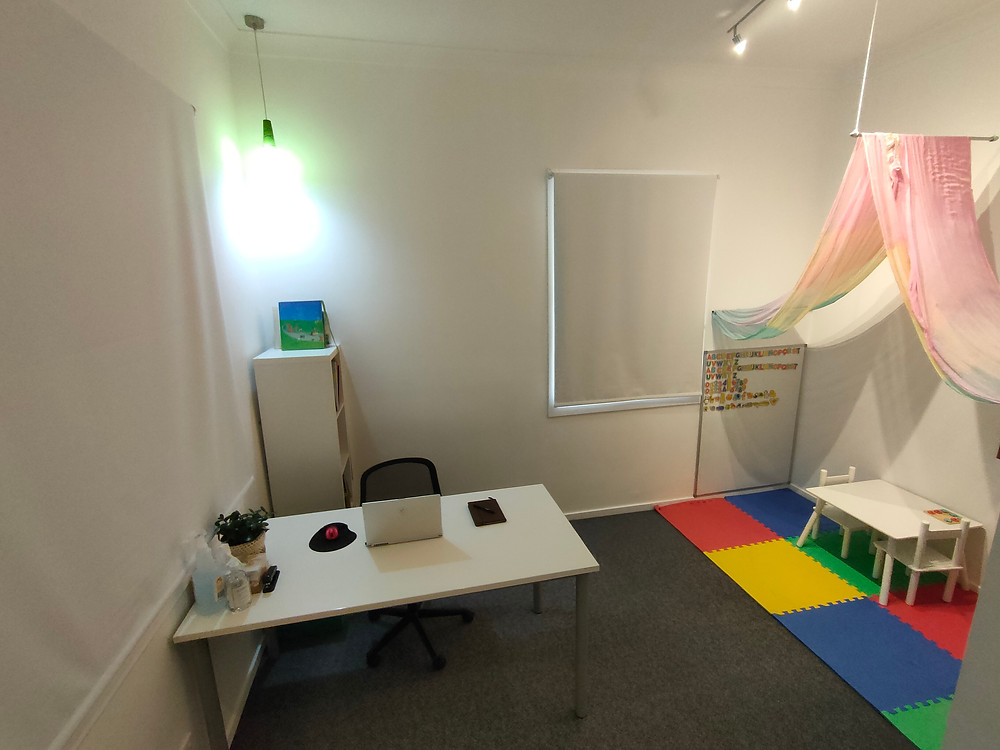 A desk with a computer and small plant are in the foreground. To the right of the photo is a children's play space with a multi-coloured jigsaw mat and a flowing rainbow curtain handing from the ceiling.