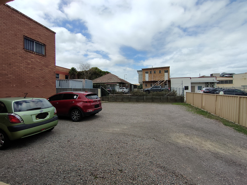 An image of 2 cars parked on a gravel block with buildings in the background. A carpark.