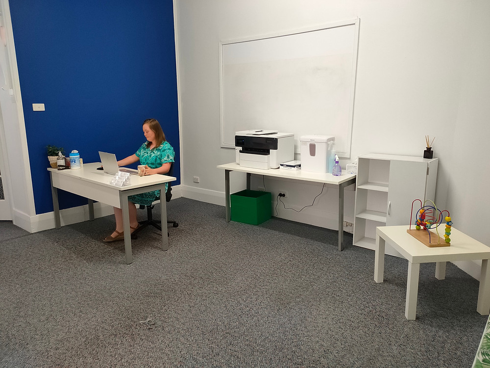 A woman with a disability sits at a reception desk against a blue wall. Behind her is a desk with a computer and shredder on it. A small child's play table is on the opposite side of the room.