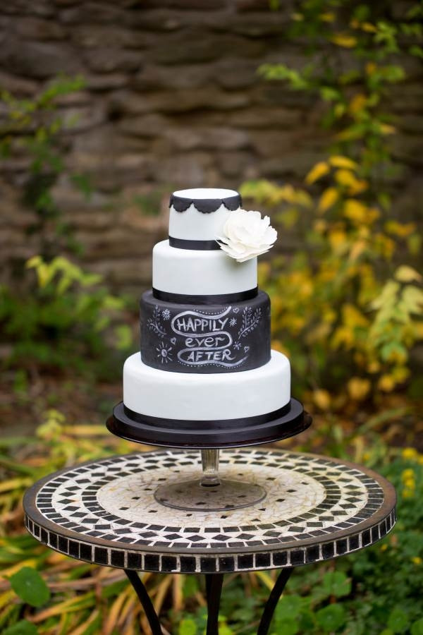 Chalkboard wedding cake with white peony outside