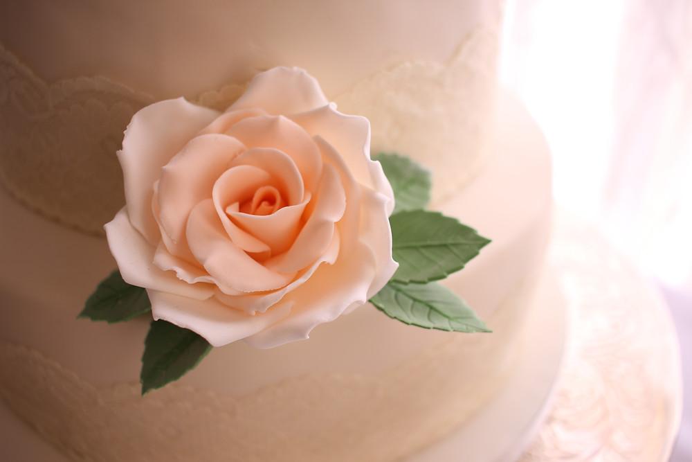 Peach sugar rose with leaves on vegan wedding cake