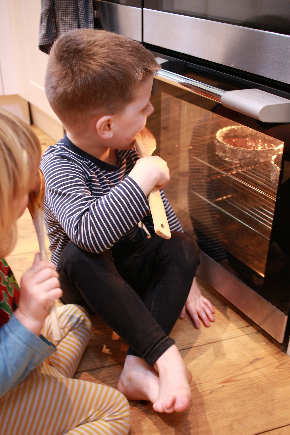 Children watching their cakes rise