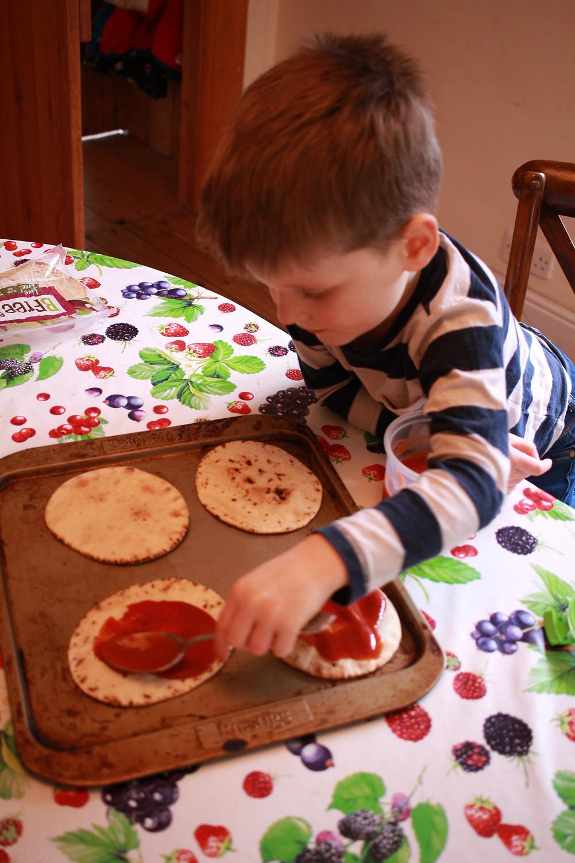 4 year old spreading passata onto a gluten-free pizza base