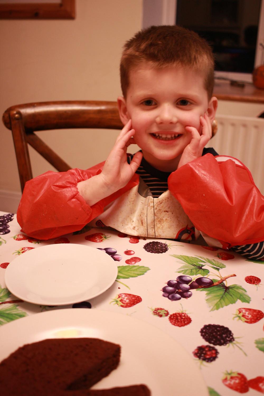 Happy boy eats slice of chocolate cake