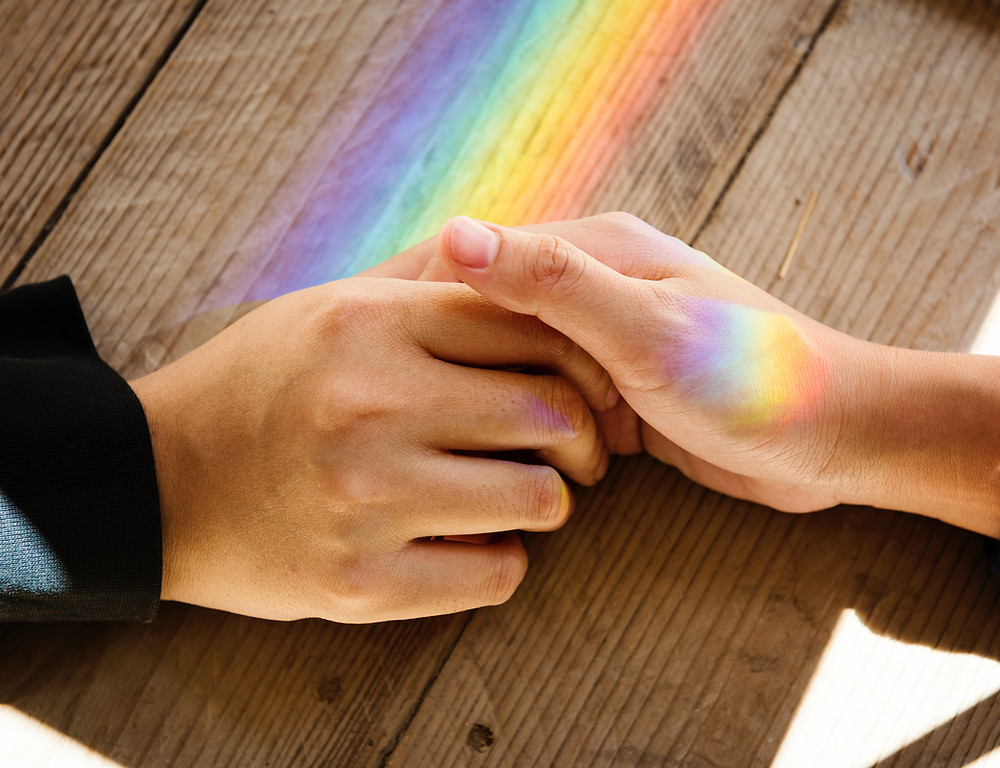 Holding hands with rainbow prism