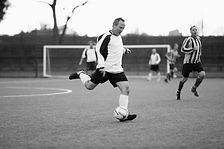 Adult male kicking soccer ball