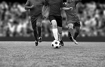Soccer players running with soccer ball