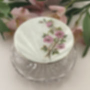 A Silver And White Enamel Topped Jar With A Pink Blossom Flower Decoration.