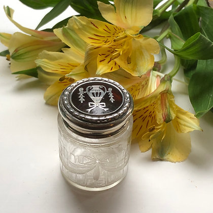 A Tortoiseshell Dressing Table Jar Decorated With a Bow.