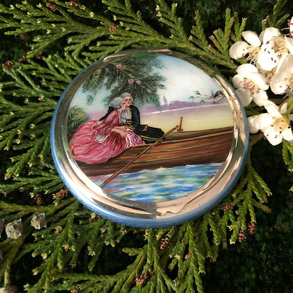 An Art Deco Silver And Enamel Compact Painted With A Romantic Scene.