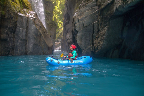 Woman pack rafting on beautiful blue New Zealand River in a Kokopelli Recon packraft. Similar to Alpacka and Blue Duck pack rafts.