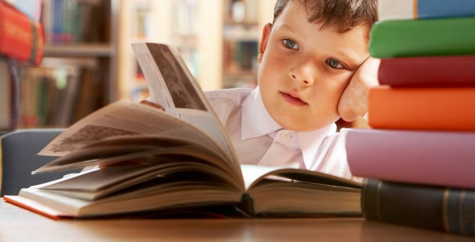 Close-up of cute boy reading book while
