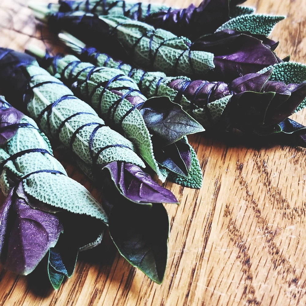 A small cluster of freshly bundled and tied bunches of sage and purple basil on a wooden surface.