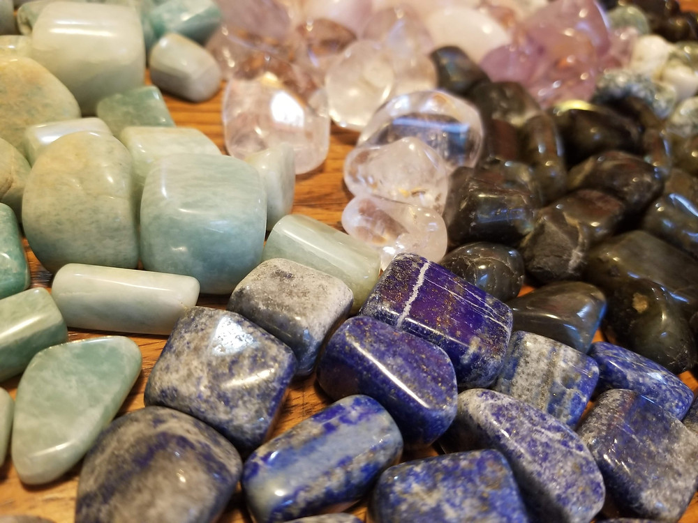 A mix of tumbled stones on a wooden surface: Adventurine, Clear Quartz, Tourmaline, Lapis, Amethyst and Tree Agate