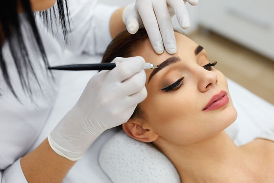Make-Up. Beautician Hands Doing Eyebrow Tattoo On Woman Face.Permanent Brow Makeup In Beau